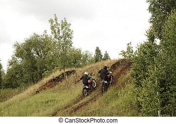 Motorcyclists climbing hill