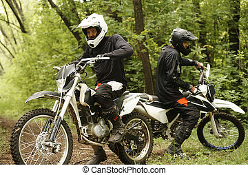 Motorcyclists in forest