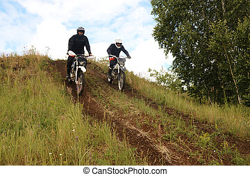 Motorcyclists moving down hill