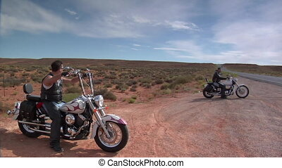 Motorcyclists resting on side of desert road