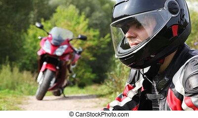 Motorcyclists sits near motorcycle, see and turn head