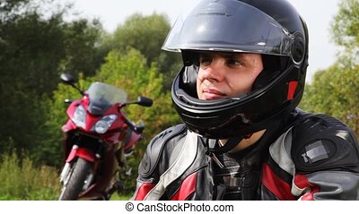 Motorcyclists sits near motorcycle, see and smile in park