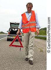 Motoring safety - Man walking backwards from his car wearing...