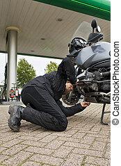 Motorist, checking the oil level - A motorist, checking the...