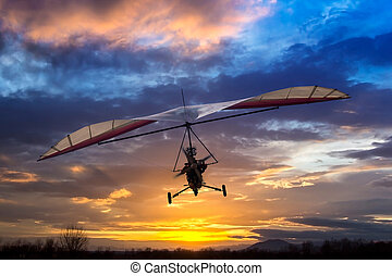 Motorized hang glider flying in the sunset