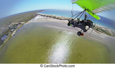 Motorized hang glider flying over sea coast GoPro Hero3 BE