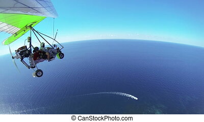 hang glider flying over sea - Motorized hang glider flying...