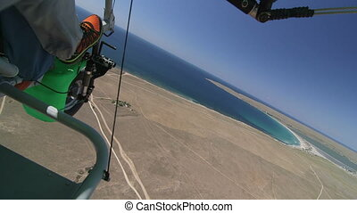 Motorized hang glider flying over seashore