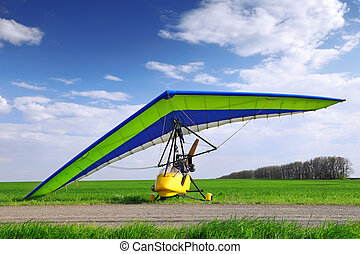 Motorized hang glider over green grass, ready to fly.