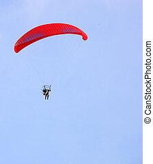 Motorized parapent against a blue sky