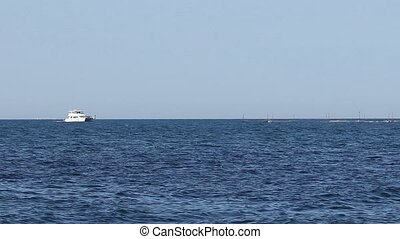 Motorized White Boat Sailing - On a calm sea and a blue sky,...