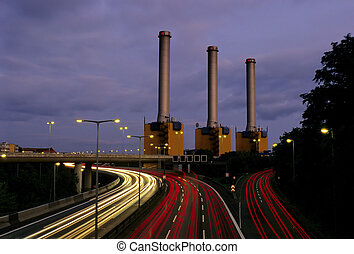 A motorway at night with a powerstation in the background, long exposure with automobile headlights