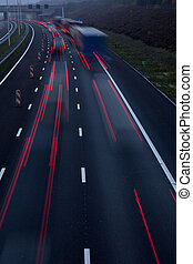 motorway at dusk with traffic of trucks and light trails