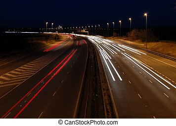 Motorway just as it goes dark with traffic travelling at speed in both directions.