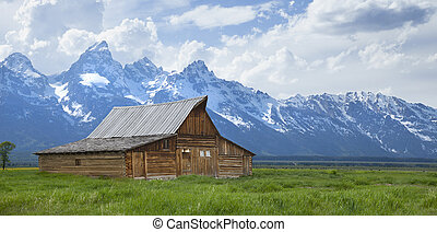 The T. A. Moulton barn sits in a grassy field beneath the Grand Teton mountains in Wyoming