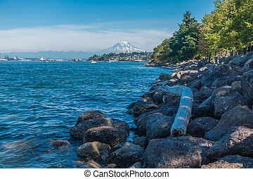 Rocks line the shore in Ruston, Washington. Mount Rainier can be seen in the distance.
