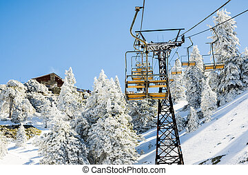Mount Baldy (Mt San Antonio) ski lift on a sunny day; snow covering the ground and the pine trees, Los Angeles county, California