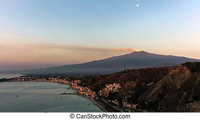Mount Etna and the Giardini Naxos coastline at dawn. View...