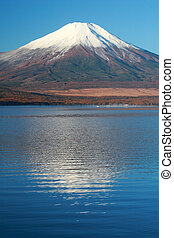 Snow-capped Mt. Fuji in Fall with reflections in mountain lake