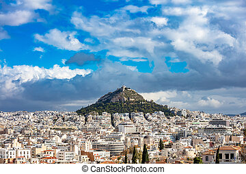 Mount Lycabettus and Athens cityscape view from Areopagus hill in Greece, blue cloudy sky