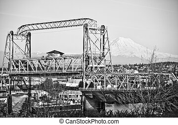 A view of Mount Rainier, Washington as seen from Tacoma with a bridge in foreground