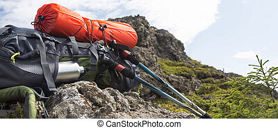 Mountain hiking equipment with backpack, isoprene, trekking sticks on a mountain rock