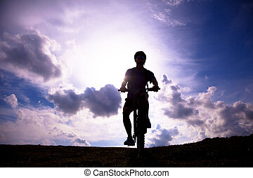 mountain bicycle rider on the hill with sunrise background