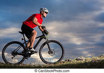 Mountain Bike cyclist riding single track outdoor with blue sky on background