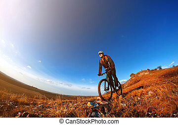 Mountain Bike cyclist riding single track outdoor with blue sky on background. Wide angle. Fisheye. Landscape with hill, blue sky and clouds. Trail. Cyclist with helmet, sunglasses and red backpack. Spring season. Countryside.