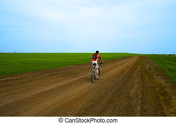 mountain bike race on ground road in the field.