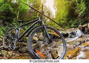 Mountain bike standing on a forest river stream.