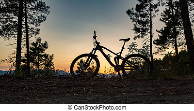 Mountain bike sunset silhouette on forest trail, inspiring landscape