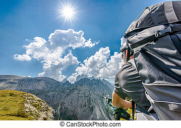 Mountain Bike Trip. Caucasian Sportsman with Backpack on His Bike in the High Mountain Landscape During Sunny Summer Day.