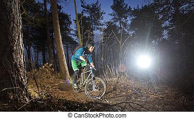 mountain biker at sunset - Mountain biker cycling through...
