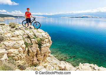 Mountain biker looking at view and traveling on bike in summer sea landscape. Man rider cycling MTB on country road or single track. Fitness motivation, inspiration in beautiful inspirational view, Croatia.