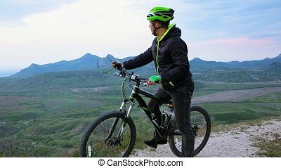 Mountain Biker Meeting Small Airplane At Hilly Terrain