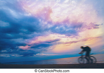 Mountain biker on beach and sunset . stormy sky