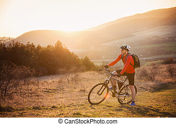 Mountain biker - Cyclist man riding mountain bike on outdoor...