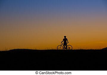 Mountain biker - Silhouette of mountain biker in sunset on...