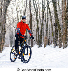 Mountain Biker Resting Bike on the Snowy Trail in Beautiful Winter Forest