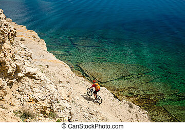 Mountain biker riding a bike on rocky trail path at sea