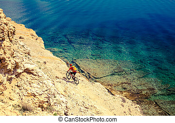 Mountain biker riding bike at the seaside trail