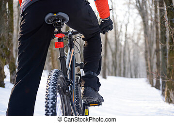 Mountain Biker Riding Bike on the Snowy Trail in Beautiful Winter Forest. Free Space for Text.