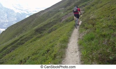Mountain biker riding downhill on small dirt road in the...