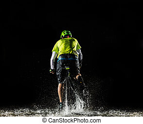 Mountain biker riding in forest stream - Mountain biker at...