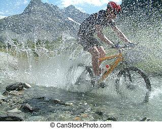 Mountain biker cycling through a river bed in a mountainous area