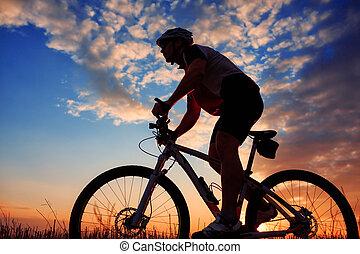 mountain biker silhouette in sunrise - Silhouette of...