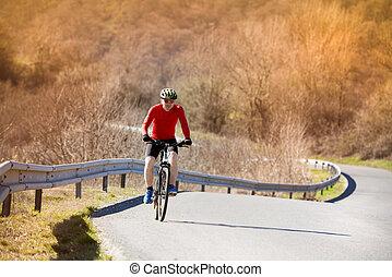Mountain biker - Cyclist man riding mountain bike on asphalt...