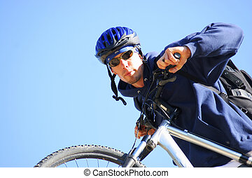 mountain biker with sunglasses and knap sack pushes bike up...