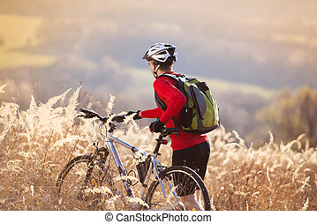 Mountain biker - Young man takes a break in a field while...